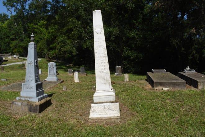 """Alexander Fulton, el fundador de Alejandría, también fue enterrado en el cementerio, pero está enterrado en un cementerio sin marcar.  Murió en 1816.  Un alto monumento blanco a su esposa Mary H.  Wells se refiere a la tumba de Fulton Hooper. """"Creemos que fue enterrado allí"""" Dijo Mike Wayne, historiador de la Asociación de Preservación del Cementerio de Historical Rapids. """"Murió primero.  Se volvió a casar con Thomas Hooper."""""""