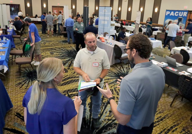 Erich Evers, center, talks with Katelyn Vande Hei and Ryan Scherer of Miller Electric during a private job fair for Clearwater Paper Employees in June at the Best Western Premier Bridgewood Resort in Neenah.