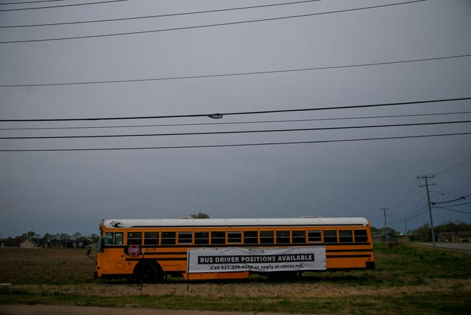 A school bus parked outside the entrance to the West Creek school campus advertises the school district's need for drivers and jobs available in Clarksville, Tenn., on Friday, April 9, 2021.