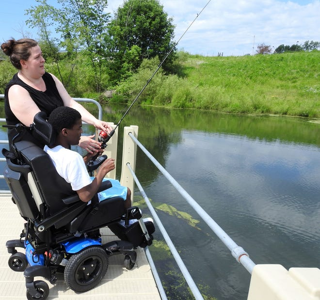 Ashlee Ederer helps Justin Woodard of Dayton to fish from a dock at Camp Echoing Hills. The facility for those with developmental disabilities started summer camps again this week after a year off due to the COVID-19 pandemic. Close to 200 campers and 30 volunteers, along with other staff, are expected at the camp outside Warsaw this season.