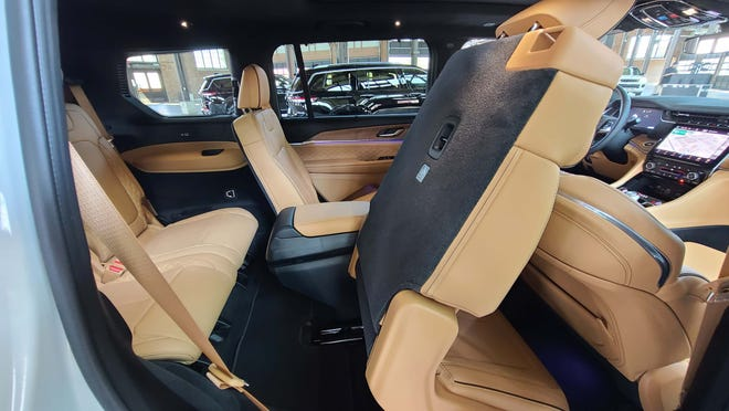 One pull on the top-seat handle and the second row seat collapses forward for access to the third row of the 2021 Jeep Grand Cherokee L.