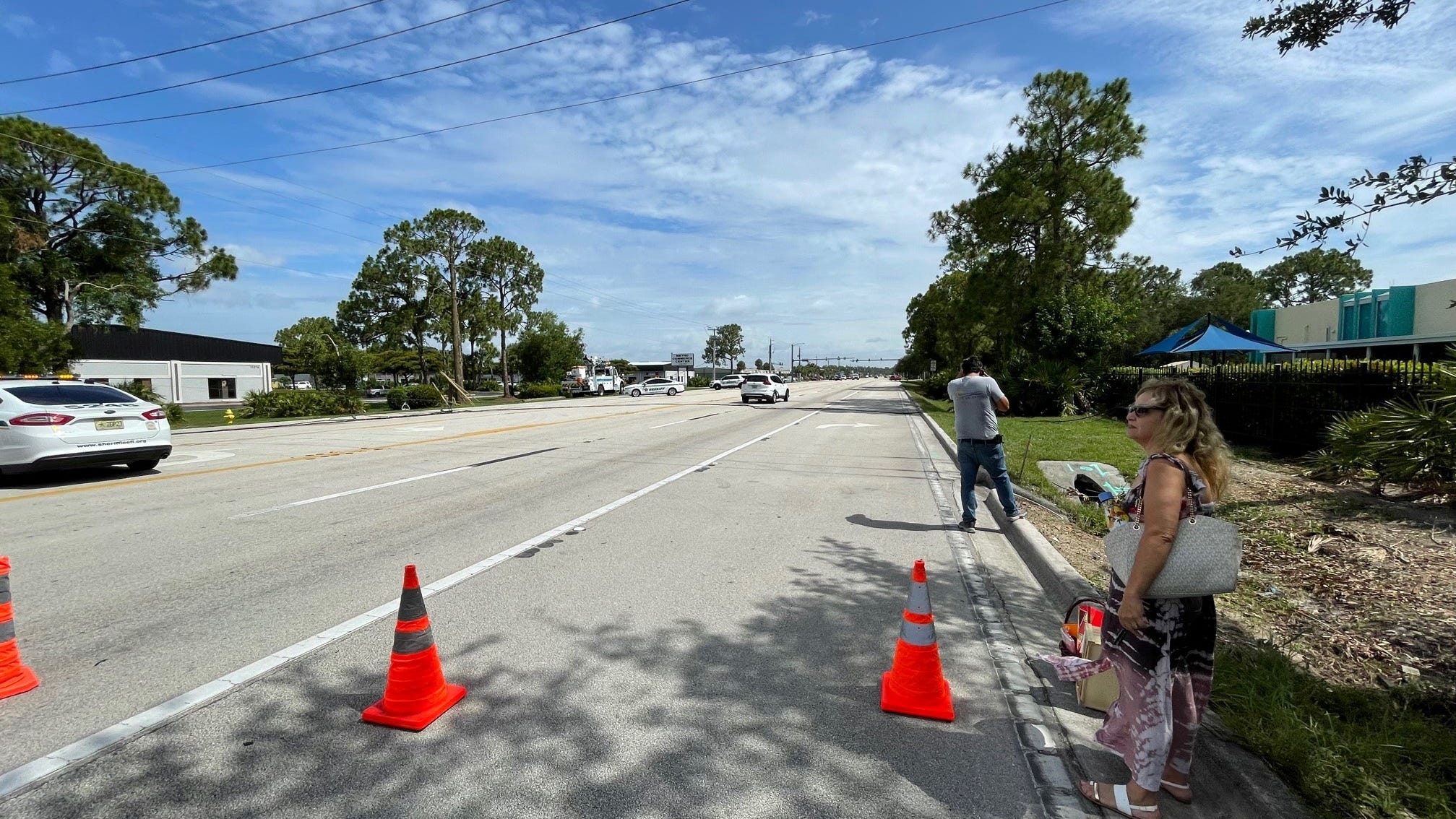 Downed utility lines crossing Metro Parkwayshut down the busy roadway Tuesday morning diverting trafficdown side streets and briefly trapping Elizeth Lopes of North Fort Myers, right, in her SUV.