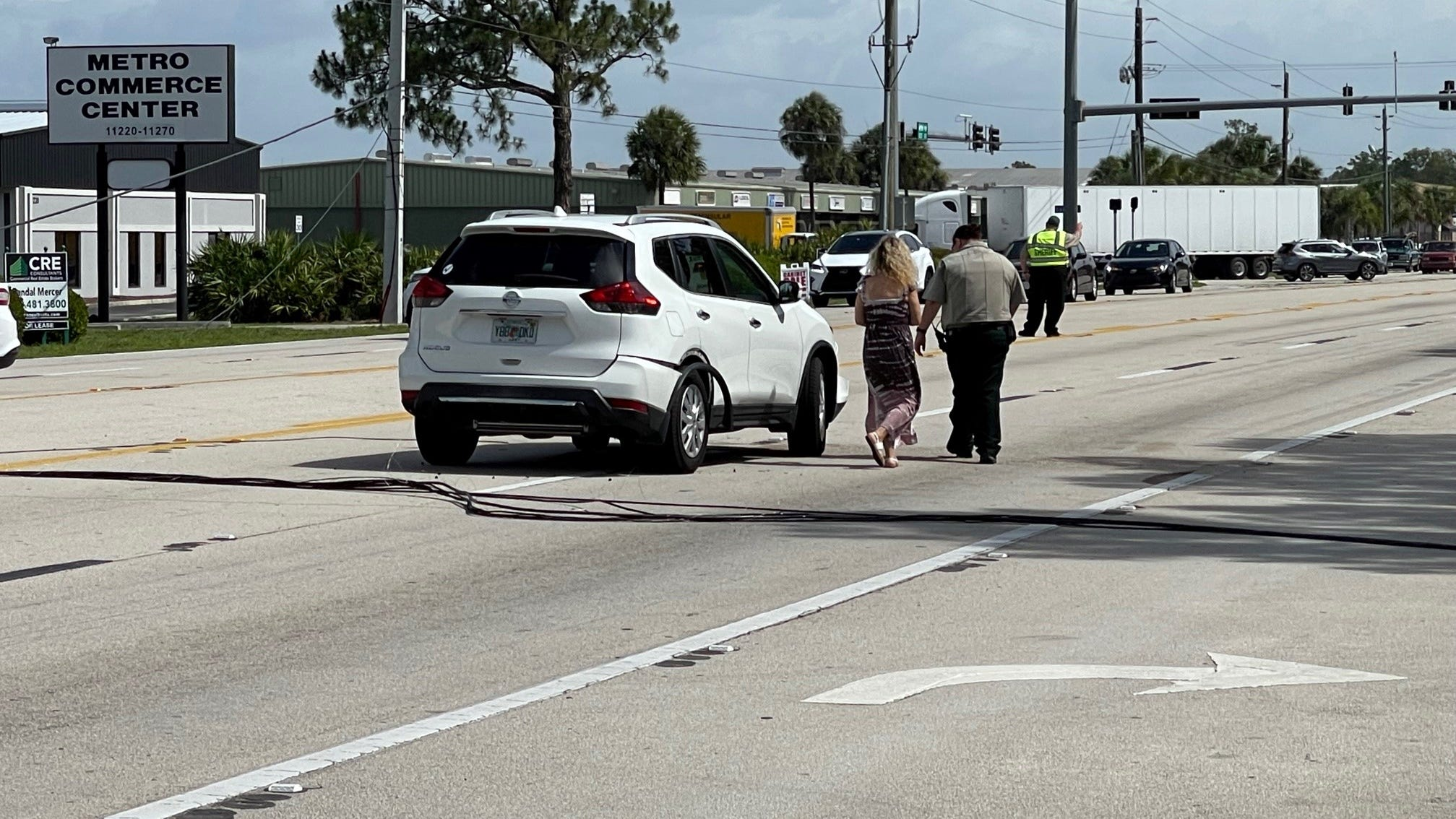 Downed utility lines crossing Metro Parkwayshut down the busy roadway Tuesday morning diverting trafficdown side streets and briefly trapping Elizeth Lopes of North Fort Myers in her SUV.