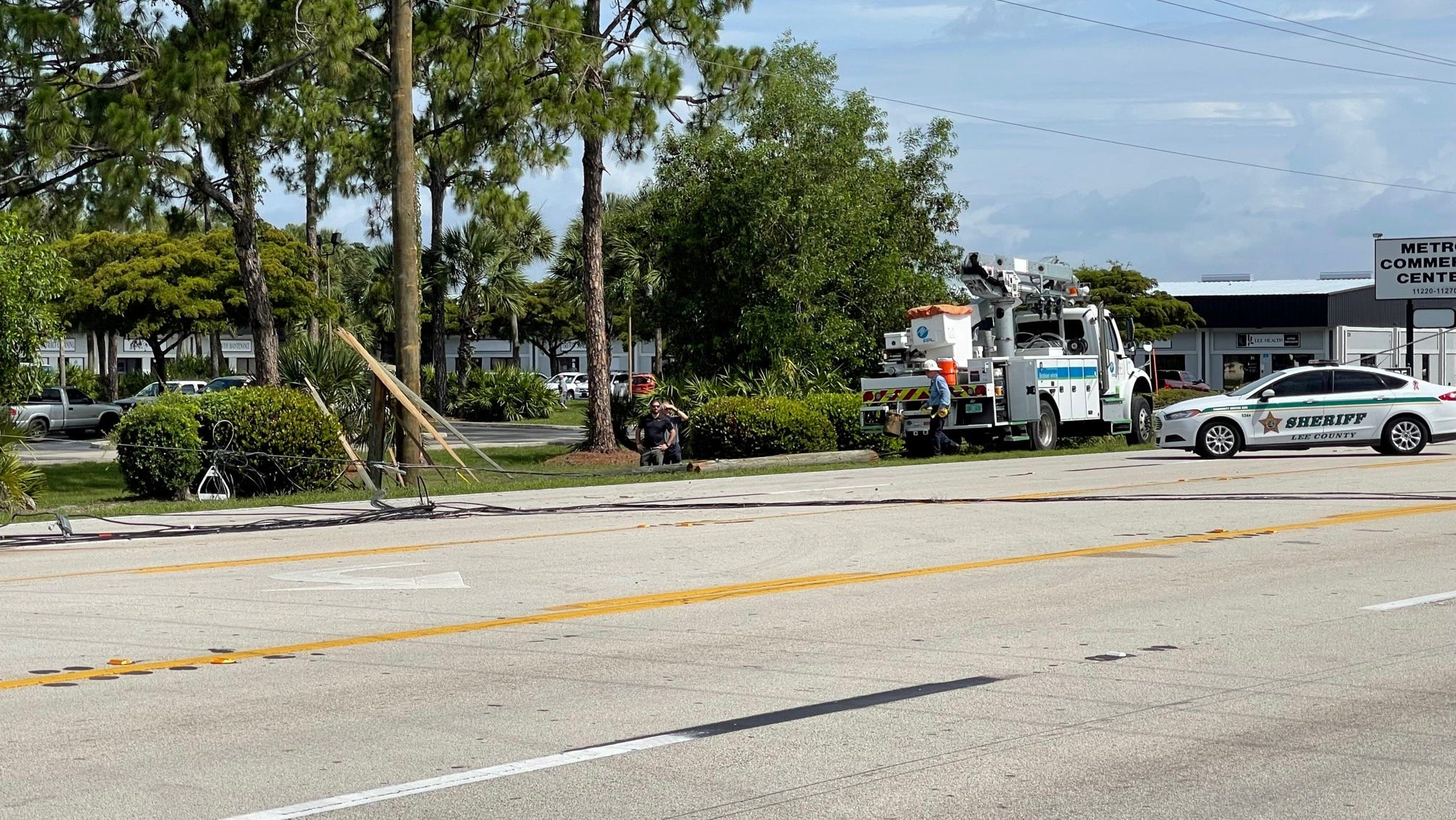 Downed utility lines crossing Metro Parkwayshut down the busy roadway Tuesday morning diverting trafficdown side streets and briefly trapping a North Fort Myers woman in her SUV/