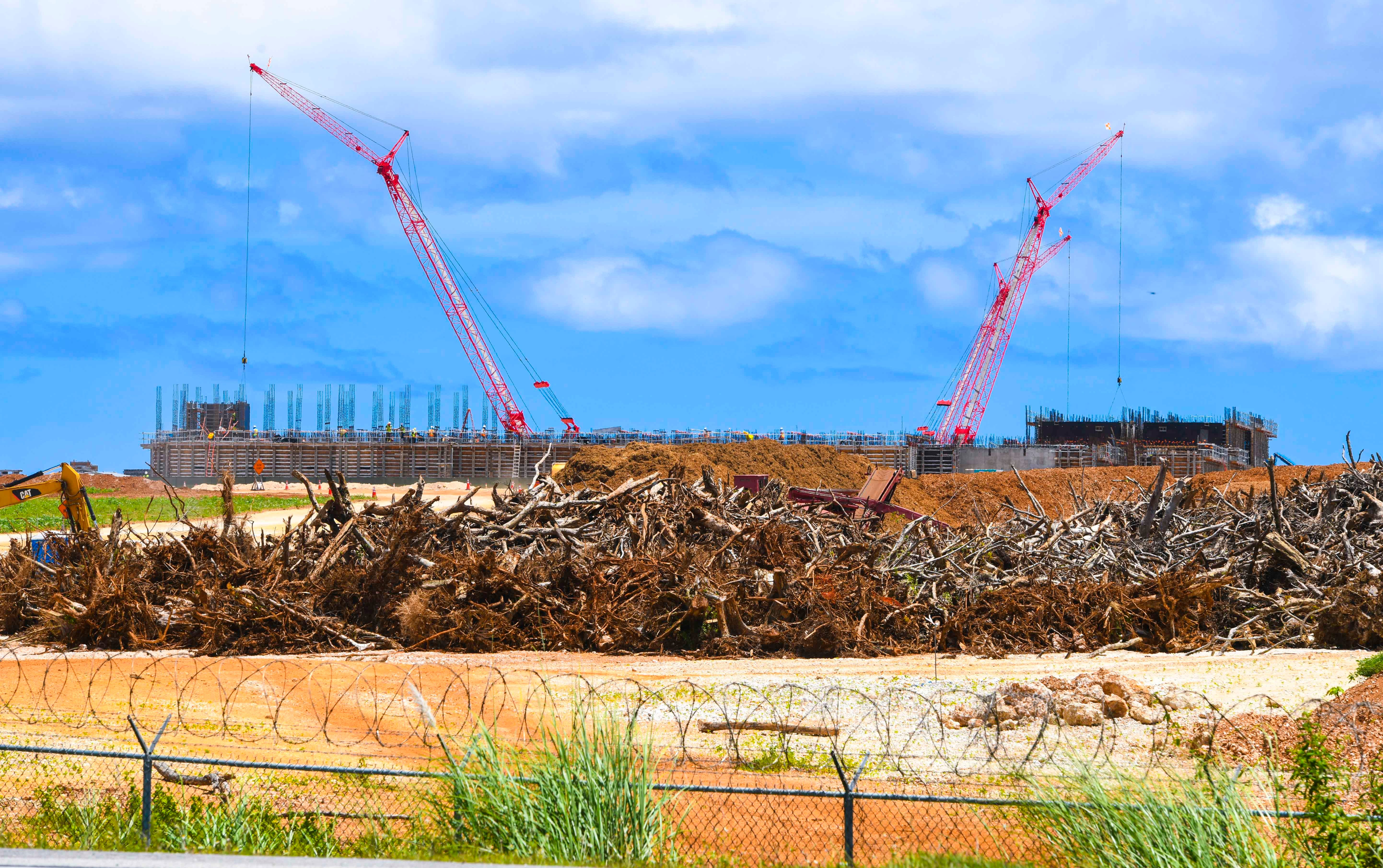 Trees and other vegetation, is piled within the fenced confines of Camp Blaz along Route 3, as building construction continues in Dededo, on Tuesday, June 15, 2021.