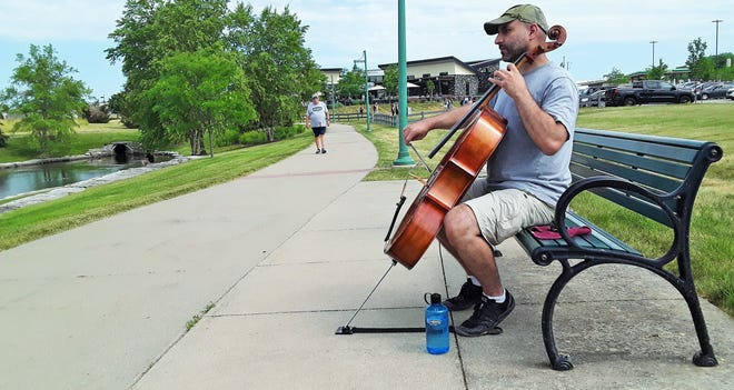 Sweltering temperatures failed to discourage Mark Awad from practicing his cello Saturday on this trailside bench at Liberty Centre Park in North Liberty, not far from the Tin Roost restaurant seen in the background. Awad teaches orchestra at the junior high and elementary levels in North Liberty for the Iowa City Community School District. He says he occasionally likes to play outside near the beautifully landscaped four-acre pond here, but these days makes sure to keep a water bottle handy.