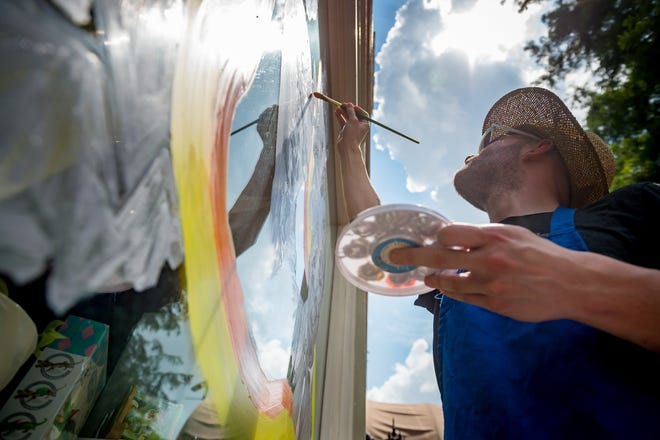 Local artist and educator Ben Koch paints a mural on the window at Beausoleil Books & Whisper Room Tuesday. Every author depicted in the muralis or was anopenly gay activist.