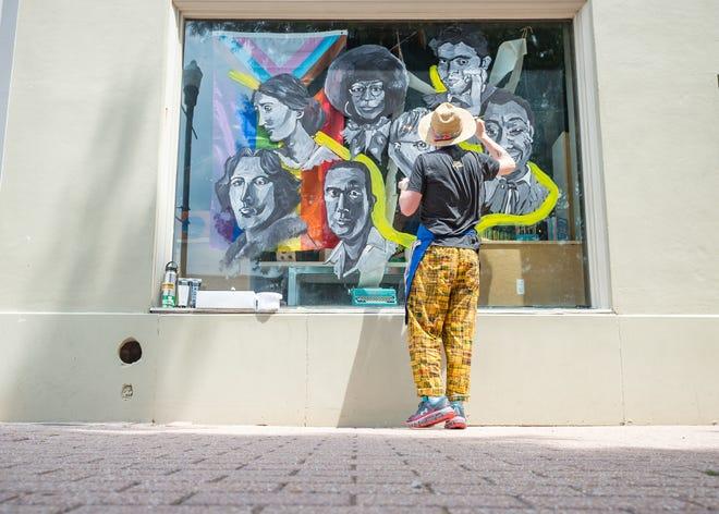 Local artist and educator Ben Koch painting window art downtown at Beausoleil Books & Whisper Room. Tuesday, June 15, 2021.