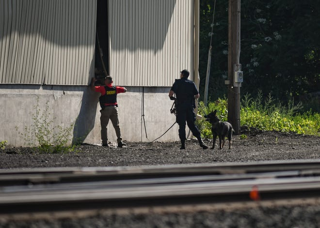 Members of the Michigan State Police and Eaton County Sheriff's Department search an area south of the railroad tracks near North Clinton Street and Union Street in Grand Ledge Tuesday morning, June 15, 2021, for a man considered armed and dangerous. MSP said a vehicle crashed into a Grand Ledge home early Tuesday morning. Six people were eventually taken into custody.
