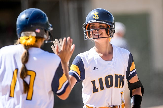 South Lyon's Grace Walters, right, celebrates her run against DeWitt with teammate Ava Bradshaw in the second inning on Tuesday, June 15, 2021, during the state quarterfinal game at Novi High School.
