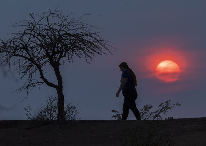 A hiker walks on a trail at Papago Park as the sun sets in Phoenix on June 14, 2021. The National Weather Service Phoenix issued an excessive heat warning for portions of south central Arizona through the week.