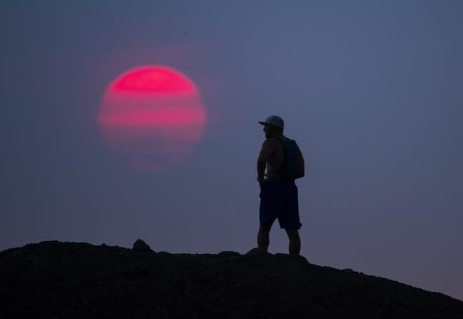 The sun glows red from smoke from the Telegraph Fire east of Phoenix as a hiker pauses on a trail at Papago Park on June 14, 2021.