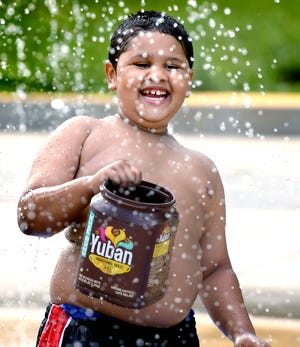 Ja'syah Donnelly, 6, of York City, fills a container at the Penn Park splash pad while visiting it with his family Monday, June 14, 2021. The sprinkling water feature is a popular spot to cool off in York City during heat waves. Bill Kalina photo
