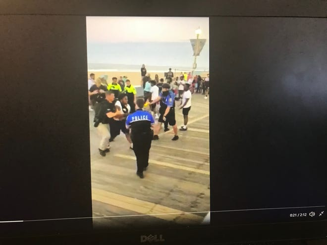 This image shows an Ocean City police officer preparing to use a Taser on an individual during a boardwalk arrest captured in viral video on Saturday, June 12, 2021.