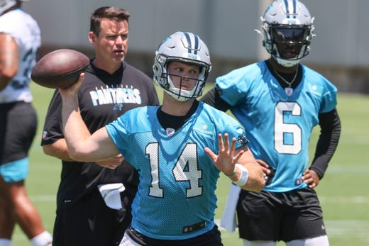 Carolina Panthers quarterback Sam Darnold (14) throws a pass as quarterback PJ Walker (6) looks on during NFL football practice in Charlotte, N.C., Tuesday, June 15, 2021.