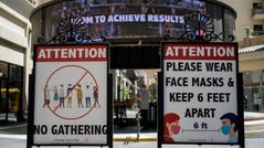 Signs with social distancing guidelines and face mask requirements are posted at an outdoor mall in Los Angeles.