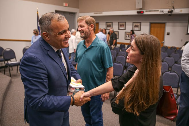 Hafedh Azaiez shakes hands with a parent at a Round Rock school board meeting Monday following his hiring as new superintendent. Because of a procedural error, trustees will have to vote again Saturday on hiring Azaiez.