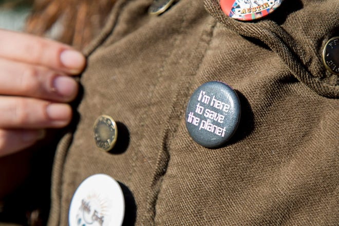 An activist for Environment Texas is shown showing off a pin before a 2019 press conference.