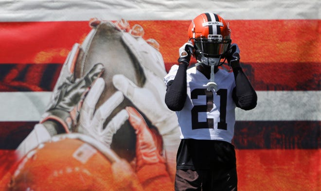 Cleveland Browns cornerback Denzel Ward (21) straps on his helmet as he takes the field during an NFL football practice at the team's training facility, Wednesday, June 16, 2021, in Berea, Ohio.