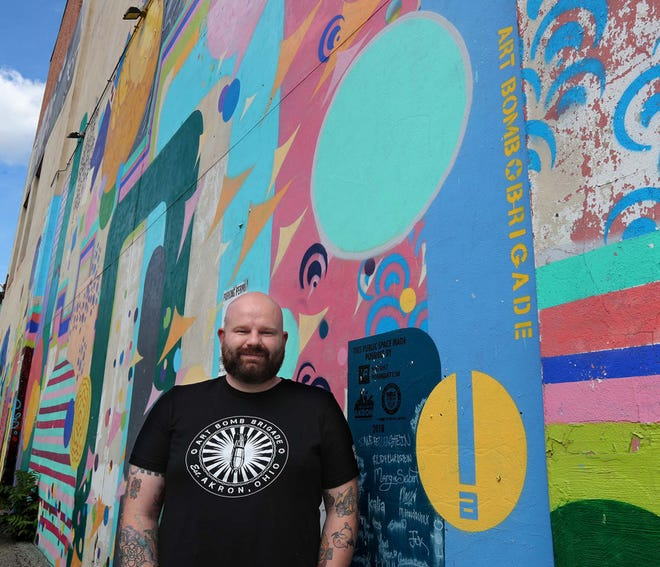Dan Coffield, a Firestone High School art teacher and community artist involved with youth programs, stands Tuesday in front of a mural that he helped to coordinate on the wall of Crave Restaurant in Akron.
