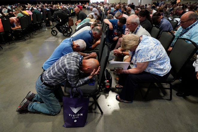 People pray during the annual Southern Baptist Convention meeting Tuesday in Nashville, Tenn.