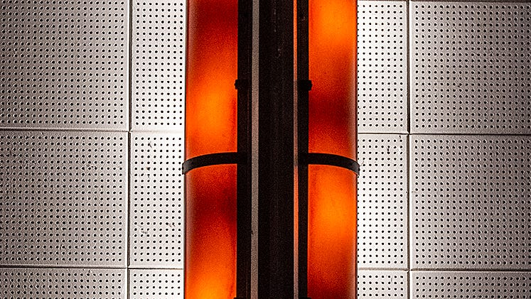 Original wall sconces, from 1925, now powered by light bulbs, adorn the walls inside the Newtown Theater.