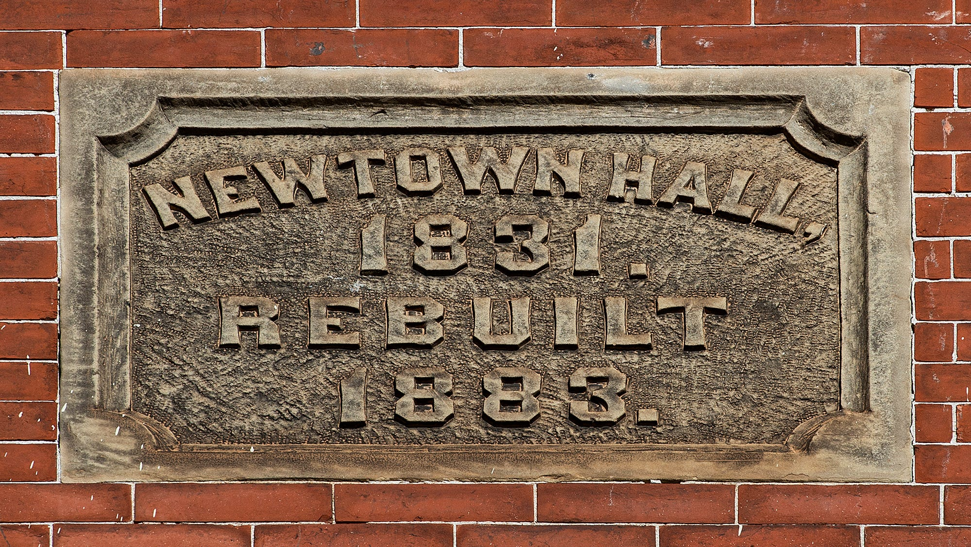 Historical marker on the front facade of the Newtown Theater.