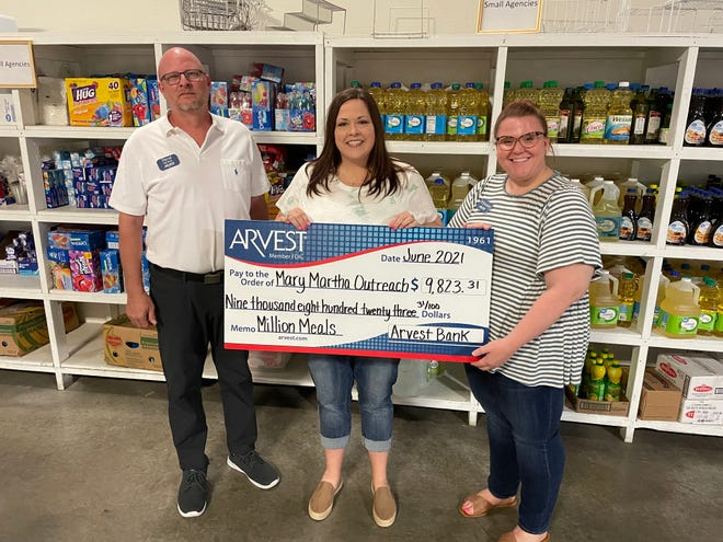 David Nickel, Arvest loan manager, left, and Whitney Watson, Arvest sales manager, right, present a check to Misty Wishall, Mary Martha Outreach executive director, to feed the hungry.