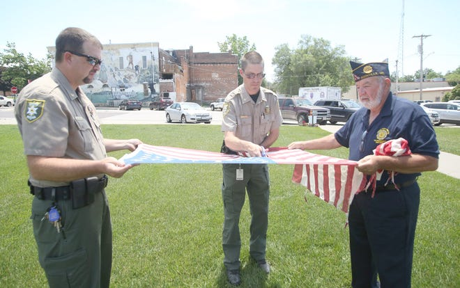 Cooper County Sheriff Chris Class, Major Kerry Webster and Sergeant of Arms Gene Walje cut up a flag that was being decommissioned Monday at Veteran's Memorial Park during Flag Day in Boonville.