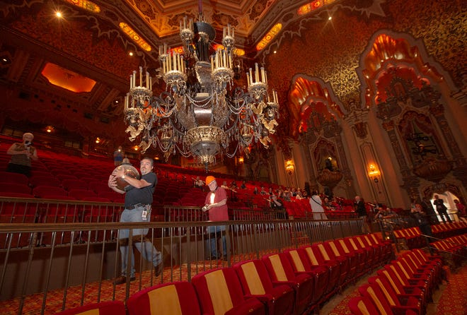 Chris Skinner, director of operations at the Ohio Theatre, carries away the bottom ball decorations on the chandelier at the theatre. The massive chandelier was lowered so it could be cleaned and light bulbs replaced. The cleaning generally happens every two years but was postponed during the pandemic. (Photo by Tim Johnson)