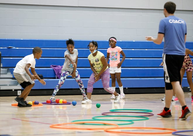 Summer campers at LiFESports camp react after the girls team beat the boys team during a relay race at Linden Community Center.