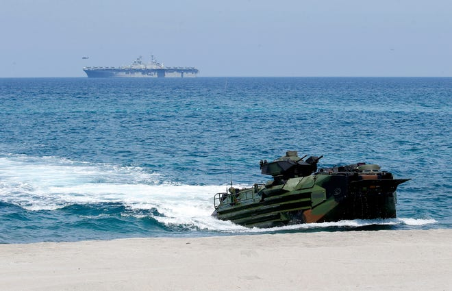 The U.S. Navy's multipurpose amphibious assault ship USS WASP cruises in the background after sending a smaller amphibious assault vehicle (foreground) ashore during a joint U.S.-Philippine military exercise in April 2019 near Manila.