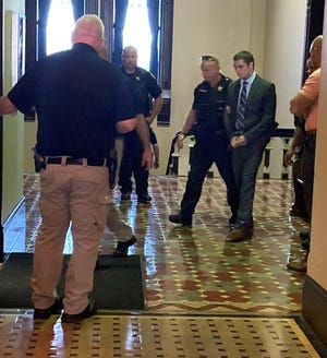 Convicted killer Jacob Harper is removed from the Guernsey County Courthouse by sheriff's deputies and bailiffs after a jury convicted him earlier in June for aggravated murder, murder and improper handling of a firearm in a motor vehicle.