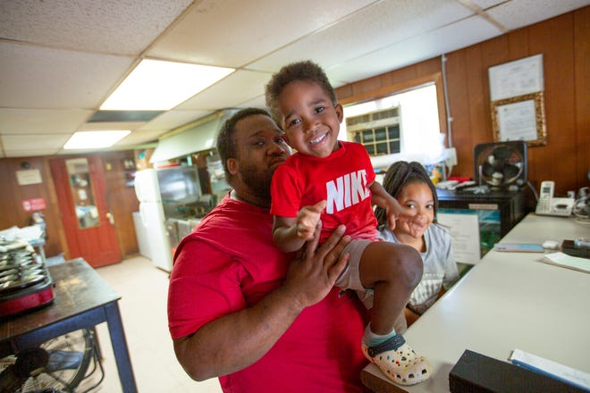 Jeremey Warren is joined by his 4-year-old son Jeremiah Warren and 13-year-old daughter Ianna Warren inside Willie's Famous Wings in Columbia, Tenn., on Tuesday, June 15, 2021. The two are spending their summer break assisting their father at the restaurant.