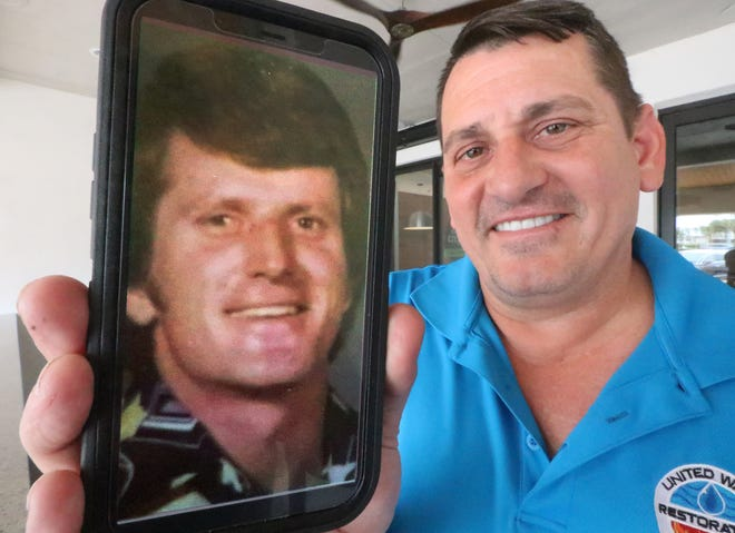 Daytona Beach native Mark Burger shows off a cellphone photograph of his biological father Tommy Leonard. Burger only met Leonard for the first time less than two years ago. This weekend, he will travel to Island Park, Idaho, to again spend time with the father that he's still getting to know.