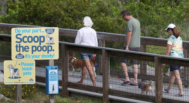 People and their dogs walk past some of the signage posted as they head for the dog beach area at Smyrna Dunes Park, Wednesday June 16, 2021. It's one of only two dog-friendly beaches, with Ponce Inlet the other location. The Volusia County Council will take a look at options for opening up the beach to pets.