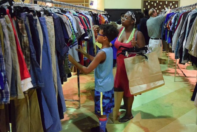 A boy checks out school clothes with his mom during a previous Back to School with BEAM event. The 2021 event is slated for July 31.