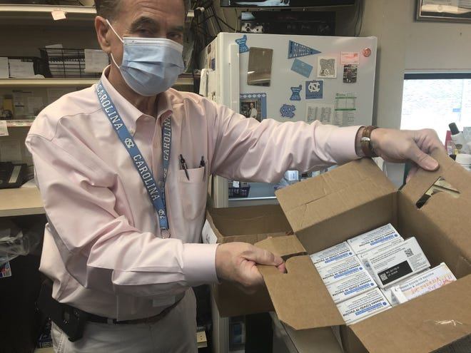 Don Thrower holds up a box of COVID-19 vaccine vials he has on hand at Medical Center Pharmacy in this Gazette file photograph.