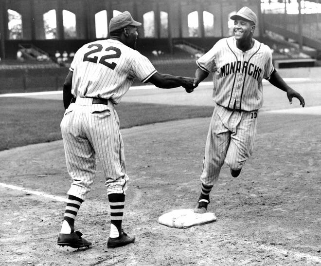 Manager John O'Neil of the Monarchs, who managed the West All Stars, greets Wesley Dennis, first baseman who hit a homer in the 7th inning, as he rounds third base on Aug. 22, 1954, at Comiskey Park during the Negro League All Star game.