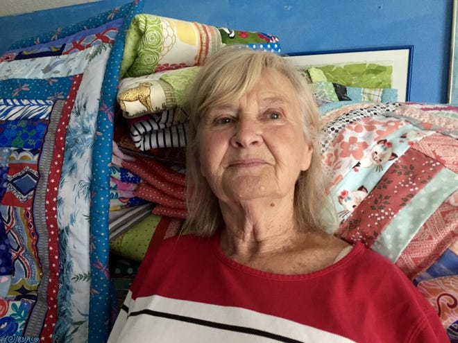 Artist and retired nurse Carla Hedges stands in front of a stack of her quilts.