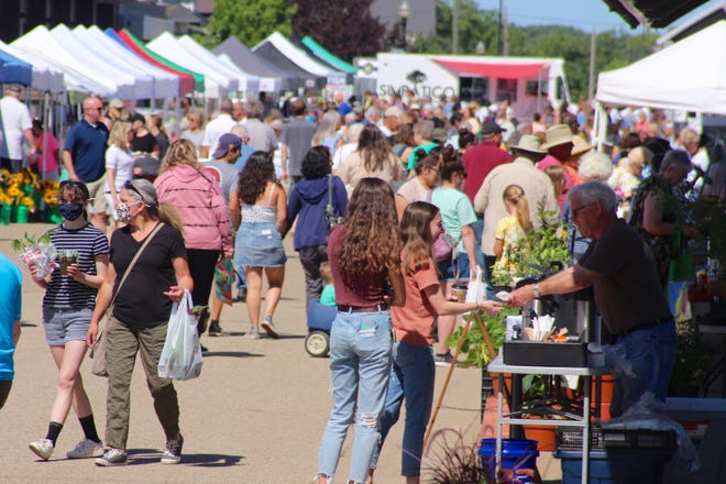 Shoppers stroll through the Holland Farmers Market on Wednesday, June 16, 2021.