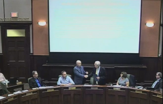 Outgoing Henderson County Manager Steve Wyatt shakes hands with Board of Commissioners Chairman Bill Lapsley during Wednesday's meeting.