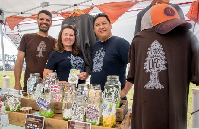 John Ingles, left, his wife, De Ingles, and Andrew Ngui, director of innovations and startups for the Greater Peoria Economic Development Council, stand in the Wild Routed Mercantile booth at the Peoria Riverfront Market. The Ingleses, with guidance from Ngui, have found success with their clothing and merchandise startup, which features stickers, T-shirts, sweatshirts and bandanas, all designed by De Ingles, a graphic designer by trade.