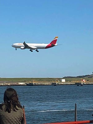 An airplane heads to Logan for landing, as seen from the deck of the Provincetown II.