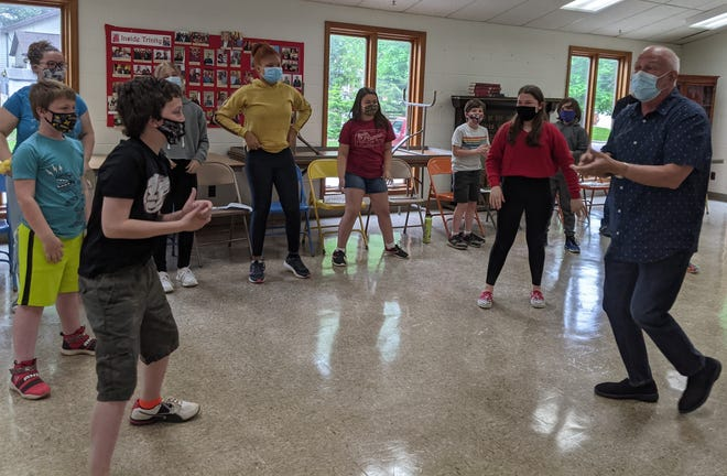 Lincoln Community Theatre Board Member and Director Tim Searby, far right, walks youth performers through a musical rehearsal for The Grunch, which opens June 25 at the Lincoln Community High School auditorium. Tickets are now on sale at the LCT website.