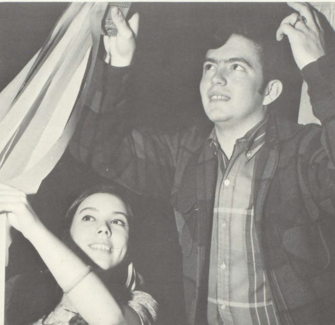 """Pictures of the Past is from the 1969 Lincoln Community High School yearbook. The photo shows Sharon and Rex playing the """"False Ceiling Game"""" while stapling crepe paper to the center ring. The carnival setting in the gym featured colors of pink, green and yellow. Couples linked arms for the Grand March and the carousel while parents and envious underclassmen watched from the balcony. Afterwards, students enjoyed a post-prom dance at the Elk's."""