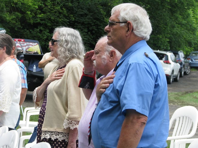 Del. Ruth Rowan, Tom Rowan, and Mineral County Commissioner Roger Leatherman stand at attention as the National Anthem is performed.
