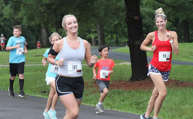 A pair of female runners join other participants of the 2019 Moberly Independence Day 5k Run/Walk fundraiser through Rothwell Park  for the high school's cross country program.The Sunday morning July 4 event will be the 29th time this 5k has taken place as the COVID-pandemic forced last year's event to cancel.