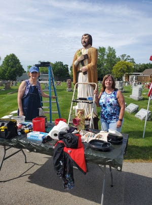 Pam Diulio (left) and Karen Jenkins prepare to work on the St. Joseph statue at St. Joseph Cemetery. This photo shows the statue before the women repainted it.
