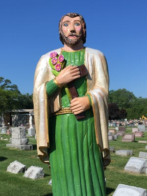 The newly repainted St. Joseph statue stands amid gravestones at the cemetery.